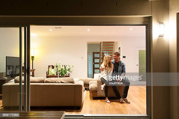 couple relaxing in their home at night. - at home stock pictures, royalty-free photos & images