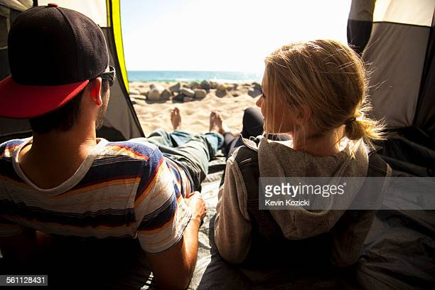 Couple relaxing inside tent on beach, Malibu, California, USA