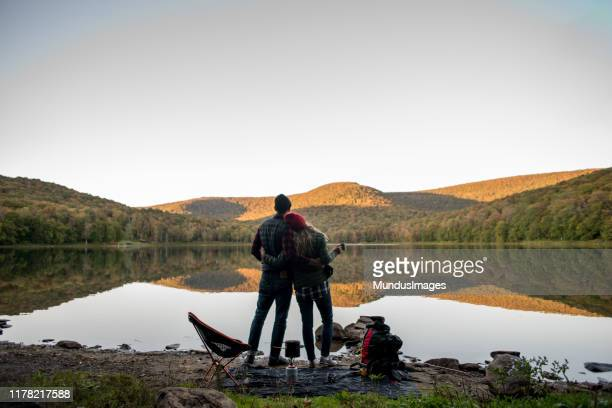 couple relaxing near a lake while camping - november stock pictures, royalty-free photos & images