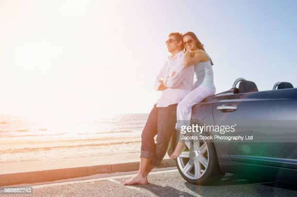 Couple relaxing near convertible in beach parking lot