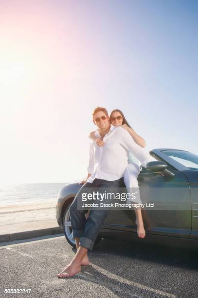 Couple relaxing near convertible in beach parking lot