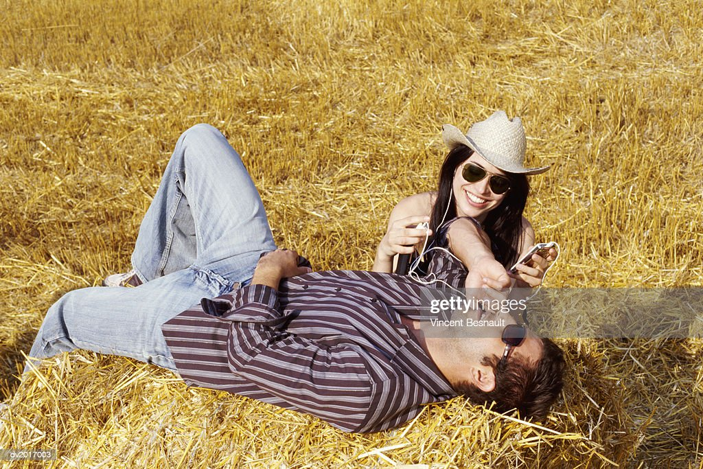 Couple Relaxing on Bales of Hay and Listening to an MP3 Player : Stock Photo