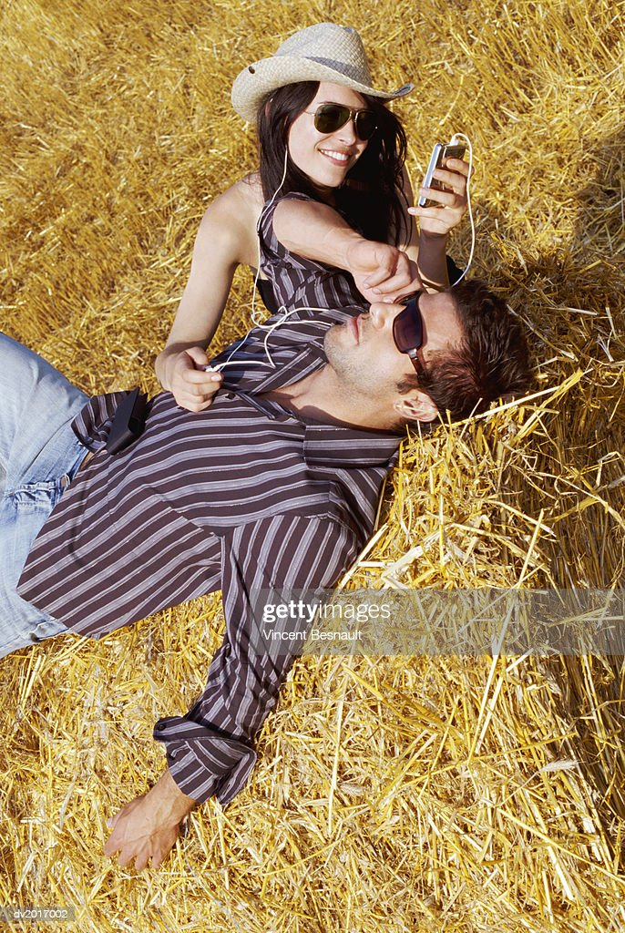 Couple Relaxing on Bales of Hay, with the Woman Listening to an MP3 Player : Stock Photo