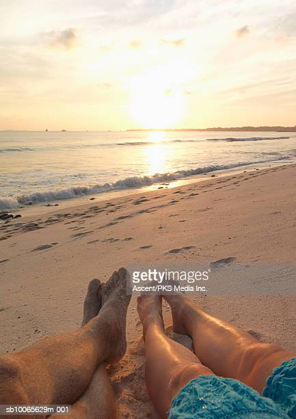 Couple relaxing on beach at sunset, low section