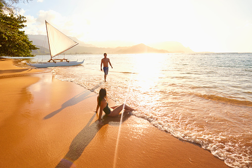 Couple relaxing on beach near sailboat - gettyimageskorea