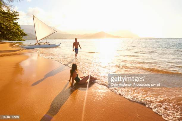 Couple relaxing on beach near sailboat
