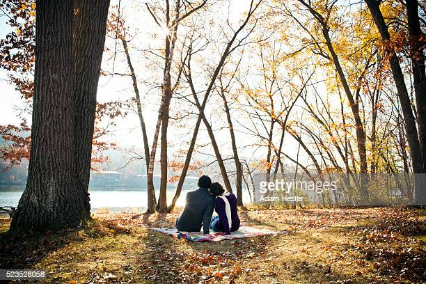 Couple relaxing on blanket in park