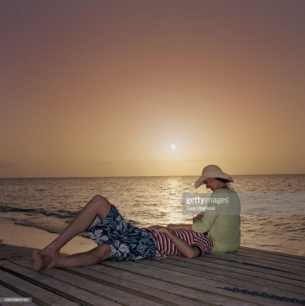 Couple Relaxing On Boardwalk Near Beach Sunset Side View