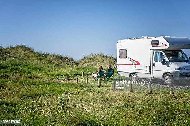 Couple relaxing on chairs alongside their campervan