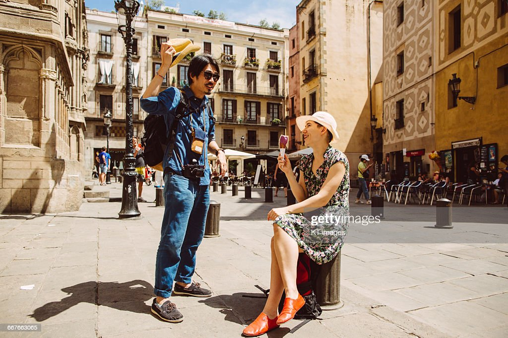 Couple relaxing on city square : Stock Photo