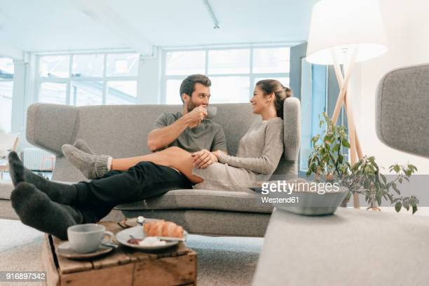 couple relaxing on couch at home having breakfast - sonntag stock-fotos und bilder