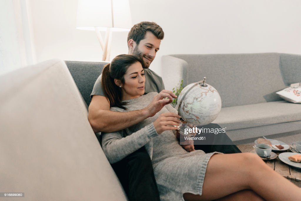 Couple relaxing on couch at home looking at globe : Stock Photo