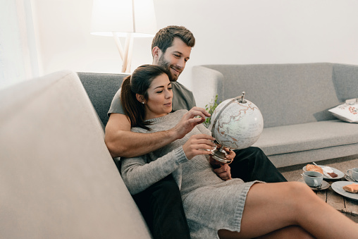 Couple relaxing on couch at home looking at globe - gettyimageskorea