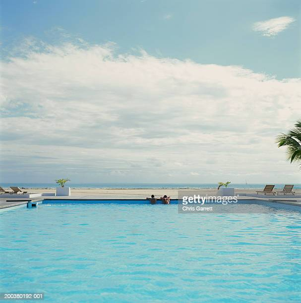 Couple relaxing on edge of pool, rear view