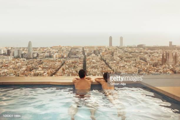 couple relaxing on hotel rooftop looking at barcelona city skyline. photo composition. - barcelona spain stock pictures, royalty-free photos & images