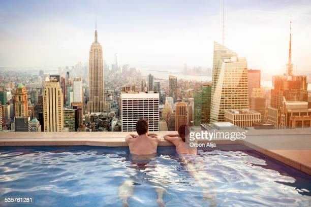 couple relaxing on hotel rooftop - stad new york stockfoto's en -beelden
