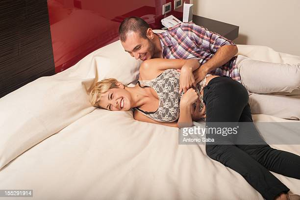 couple relaxing on hotel room bed - kitzeln stock-fotos und bilder