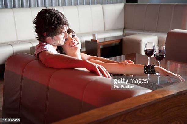 Paar entspannenden auf sofa im Wohnzimmer mit Rotwein auf Tisch