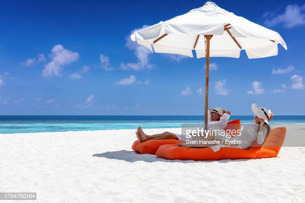 couple relaxing on mattress under parasol at beach - parasol stock pictures, royalty-free photos & images