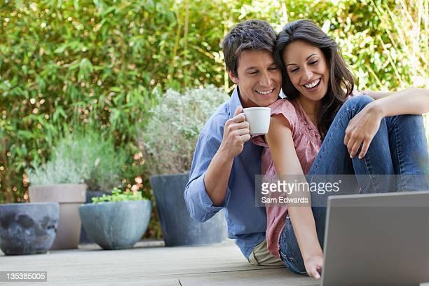 couple relaxing on patio with laptop and coffee - 30 39 jaar stockfoto's en -beelden