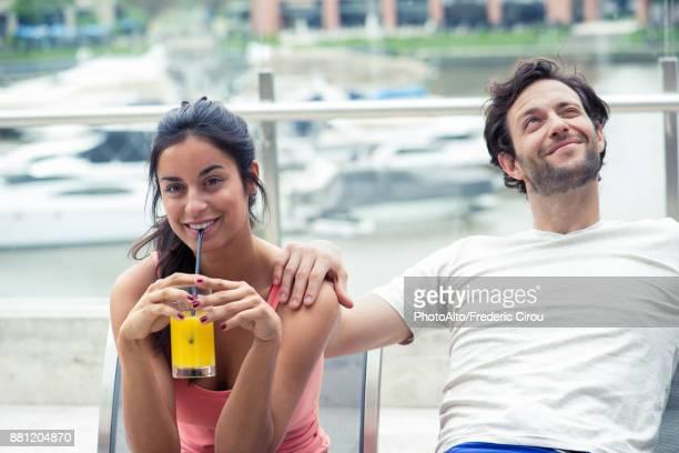 couple relaxing on patio, woman drinking juice - kaltes getränk stock-fotos und bilder