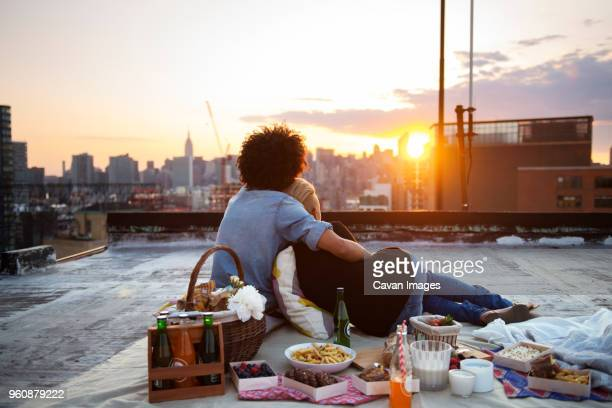 couple relaxing on rooftop against sky during picnic - dach stock-fotos und bilder