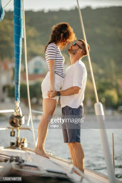 couple relaxing on sailing - miljko stock pictures, royalty-free photos & images