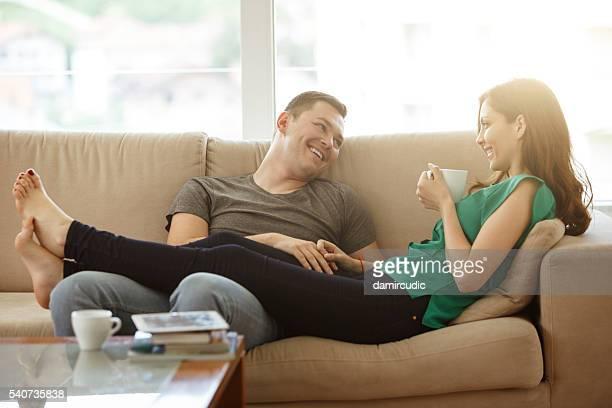 Coppia rilassante sul divano con il loro nuova casa