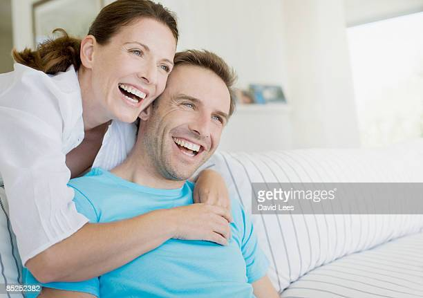 Couple relaxing on sofa, portrait, smiling