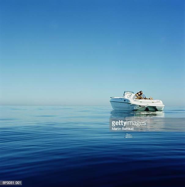 Couple relaxing on speedboat