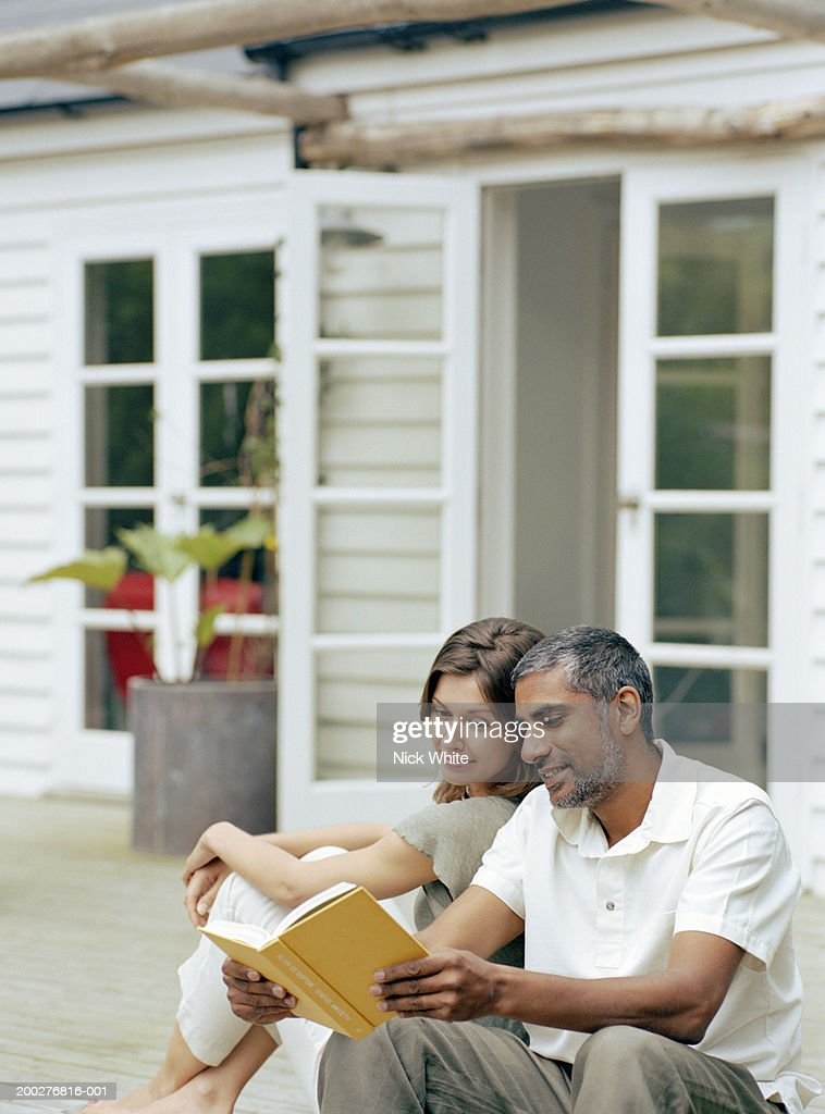 Couple relaxing on steps outside home, man holding open book : Foto de stock