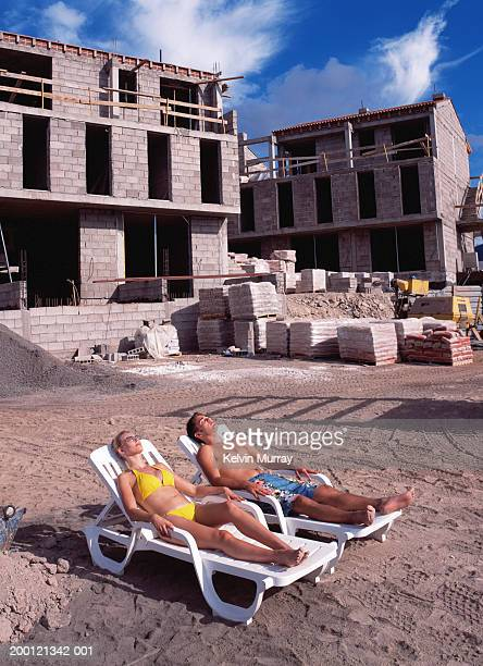 couple relaxing on sun loungers by building under construction - inconvenience stock pictures, royalty-free photos & images
