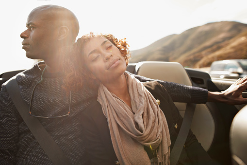 Couple relaxing on the backseat of convertible car - gettyimageskorea