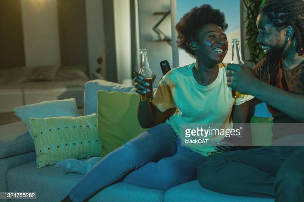 couple relaxing on the couch at home, watching sports and cheer for their team - international team soccer stock pictures, royalty-free photos & images