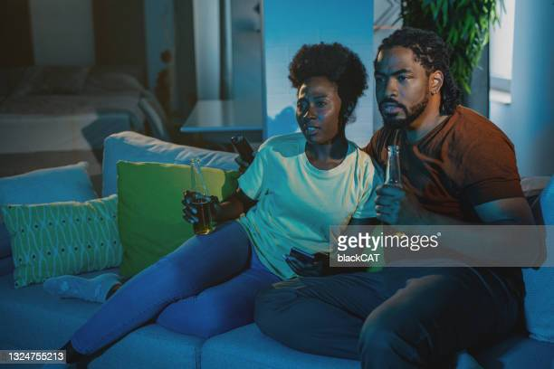 couple relaxing on the couch at home, watching sports and cheer - international team soccer stock pictures, royalty-free photos & images