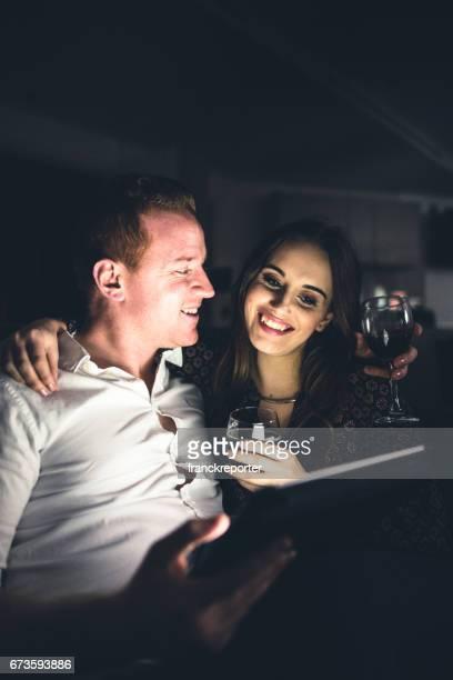 タブレットを使用してカップル自宅のソファでリラックス