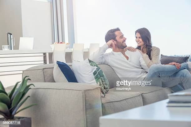 couple relaxing on the sofa. - couples stock pictures, royalty-free photos & images