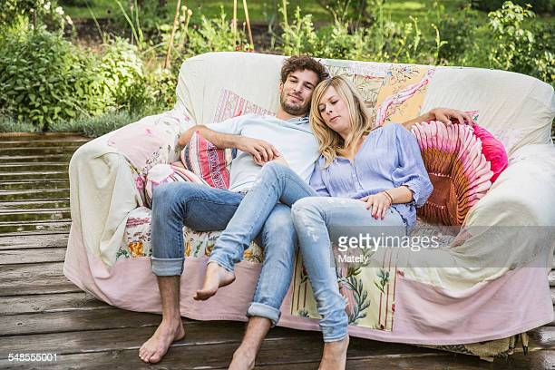 Couple relaxing on vintage sofa in garden