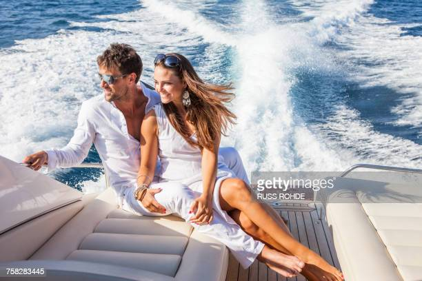 couple relaxing on yacht, on water, looking at view - segeljacht stock-fotos und bilder