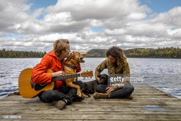 couple relaxing outdoor with dogs by the lake - stringed instrument stock pictures, royalty-free photos & images