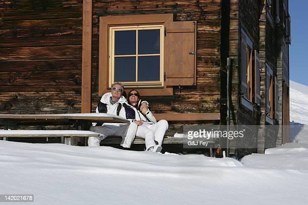 Couple relaxing outdoors at ski chalet