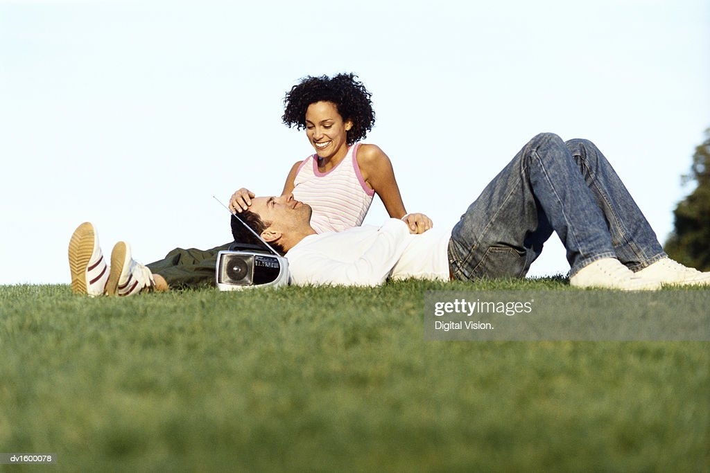 Couple Relaxing Outdoors, with the Man Lying with his Head in the Lap of the Woman, who is Stoking his Head : Stock Photo