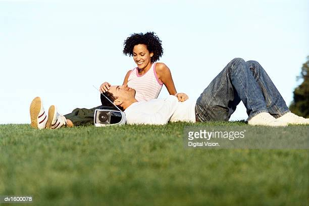 Couple Relaxing Outdoors, with the Man Lying with his Head in the Lap of the Woman, who is Stoking his Head