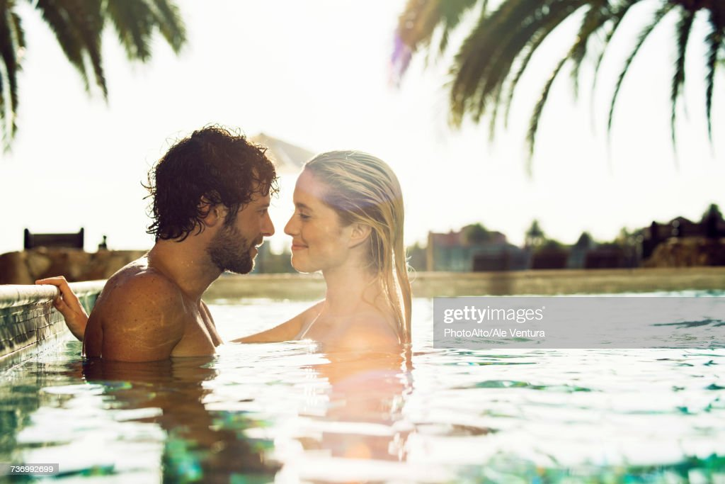 Couple relaxing together in resort swimming pool : Stock Photo