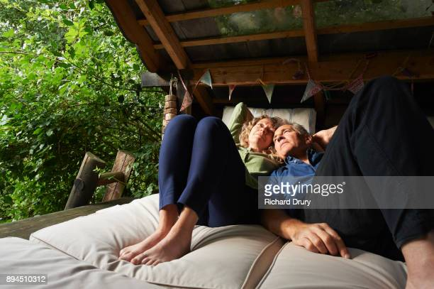 Couple relaxing together in their treehouse
