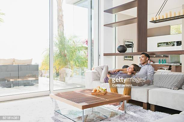 Couple relaxing together on sitting room sofa