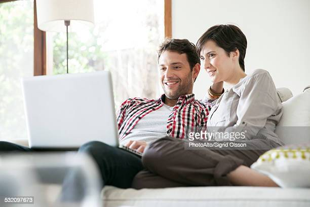 Couple relaxing together on sofa with laptop computer