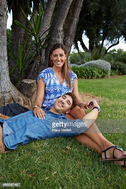couple relaxing under tree in park - klaus vedfelt mallorca stock pictures, royalty-free photos & images