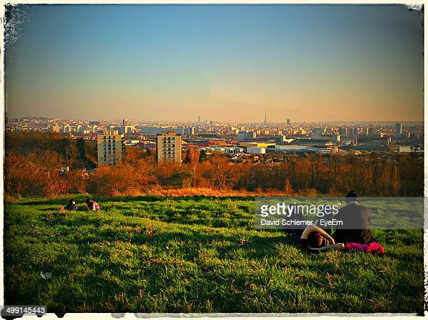 Couple relaxing while children playing in park against cityscape