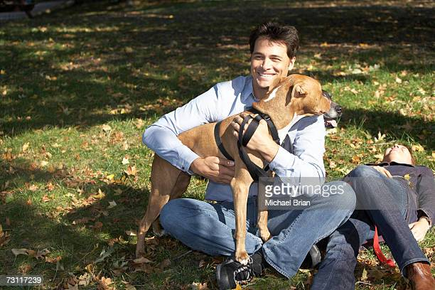 couple relaxing with dog in park - パグル犬 ストックフォトと画像